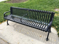 Beautiful black metal park bench in ornate style for romantic rest with date. People that need rest from exercising in park,Nice bench for relaxing & tranquil moments surrounding green grassy lawn.