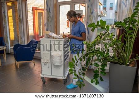 Beautiful black nurse distributes medicine.medicine,hospital,hospital corridor,nursing student,nursing school,nursing home,health care,medicine cabinet,diversity,african woman,black woman,nurse,happy,