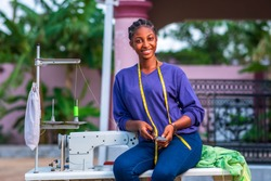 Beautiful Black seamstress sitting on sewing machine with yellow measuring tape around neck and smiling looking cheerful,looking at camera
