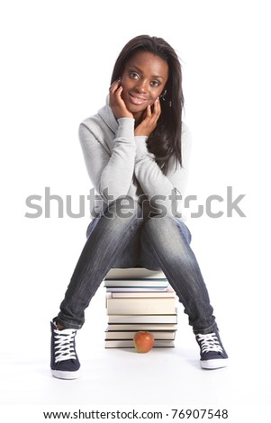 Beautiful black student girl on top of her school work. Smiling and sitting on a pile of books, girl is wearing grey hoodie sweater, blue jeans and sneakers.