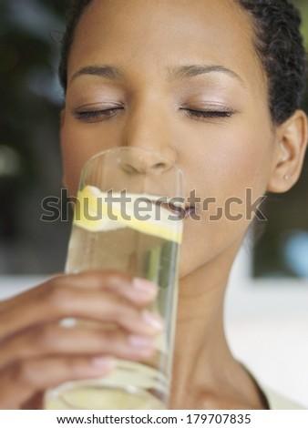 Beautiful black woman drinking water with lemon