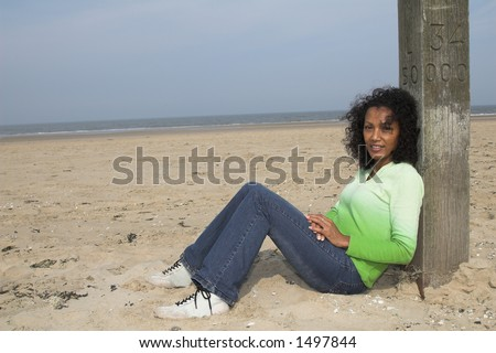 Beautiful black woman leaning against a pole on the beach enjoying the wind and sunshine