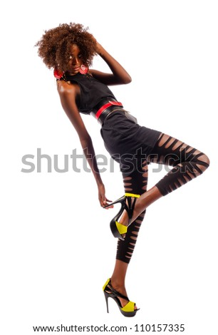 Beautiful black woman leans back as she raises her foot and grabs her heel while isolated on a white background.