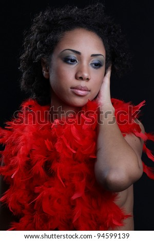 Beautiful black woman posing in a studio playing with a red feather. #94599139