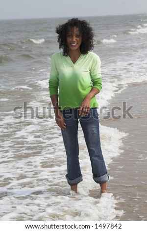 Beautiful black woman standing in the surf getting her jeans wet