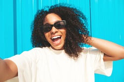 Beautiful black woman with afro curls hairstyle.Smiling hipster model in white t-shirt.Sexy carefree female posing in the street near blue wall in sunglasses.Cheerful and happy.Taking Pov selfie photo