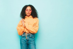 Beautiful black woman with afro curls hairstyle.Smiling model in orange hoodie and trendy jeans clothes.Sexy carefree female posing near blue wall in studio.Tanned and cheerful in sunglasses.Duck face