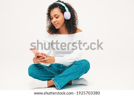 Beautiful black woman with afro curls hairstyle.Smiling model in sweater and jeans.Sexy carefree female listening music in wireless headphones.Sitting in studio on white background.Holding smartphone