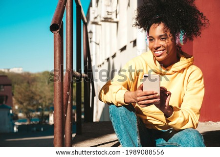 Beautiful black woman with afro curls hairstyle.Smiling model in yellow hoodie.Sexy carefree female enjoying listening music in wireless headphones.Posing on street background at sunset.Holds phone