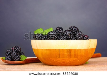 beautiful blackberries in wooden bowl on gray background