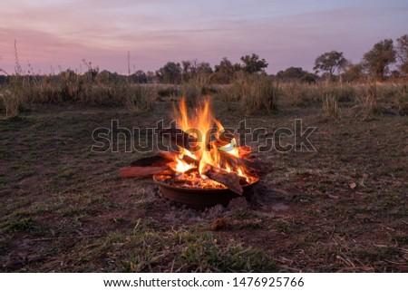Beautiful Blazing Campfire at Dusk in the Nature of the Savannah near the Okawango, Namibia, Africa #1476925766