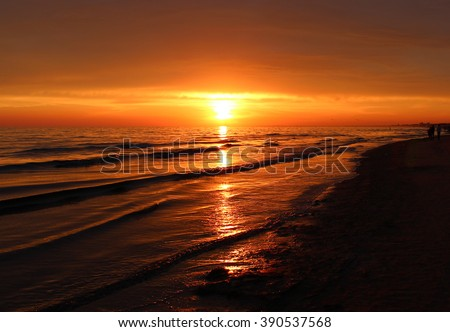 Beautiful blazing sunset at black sea & orange sky above. Gold sea sunset landscape. Sea sunset background. Amazing sunset view on the beach. Summer sea sunset waves and red sky. Sunset sea postcard.