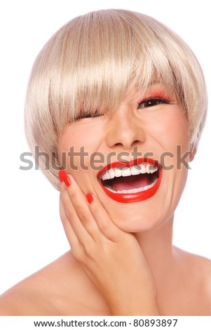 Beautiful blond asian girl with stylish make-up and hairdo laughing, on white background - stock photo