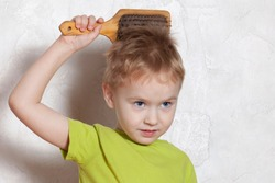 Beautiful blond baby boy brushing his golden hair with a wooden comb, pretty grimacing. Indoors, white plastered wall background, copy space.