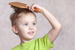 Beautiful blond baby boy brushing his golden hair with a wooden comb, pretty smiling. Indoors, white plastered wall background, copy space.