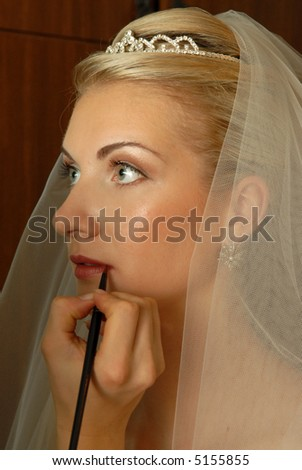 Beautiful blond bride preparing for the wedding and make-up