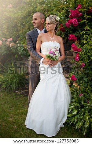 Beautiful blond bride with smiling handsome groom standing in the garden with red roses.Happy, laughing, looking into the sun, just married.