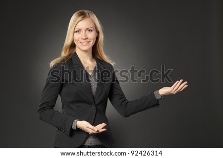 Beautiful blond business woman showing copy space over grey background