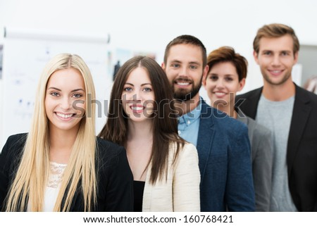 Beautiful blond businesswoman with a beaming confident smile heading up a successful team of motivated young business men and women posing in a receding row