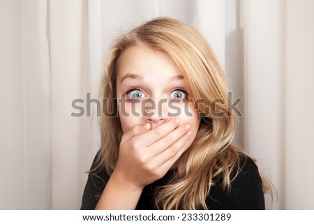 Beautiful blond Caucasian surprised girl opened her eyes wide and covers her mouth with her hands, closeup studio portrait