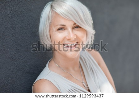 Beautiful blond caucasian woman with stylish haircut looking cheerfully in the camera on a blurred blue background #1129593437