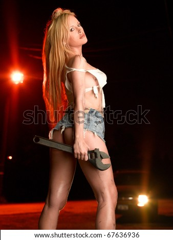 Beautiful blond fashion model wearing ripped white tank top and short denim skirt covered with grease and dirt holding large wrench at night light by red colored street lamp.