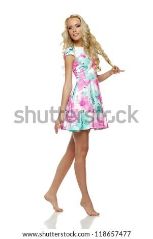 Beautiful blond female in full length posing in summer dress over white background