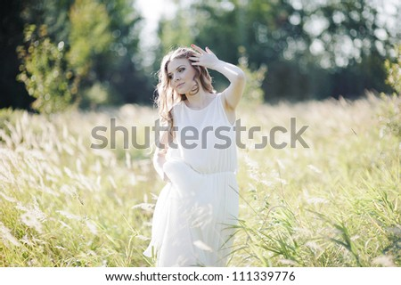 Beautiful blond girl goes trough high grass on the field.