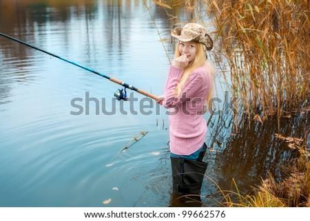 beautiful blond girl in pink sweater fishing