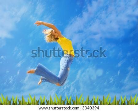 Beautiful blond girl jumps over green grass