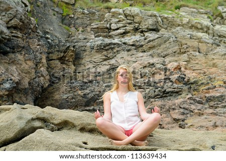 Beautiful blond girl meditate on the beach