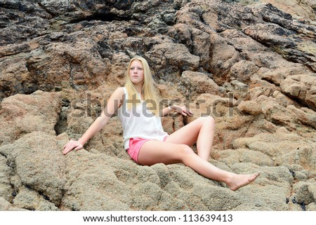 Beautiful blond girl posing on the beach