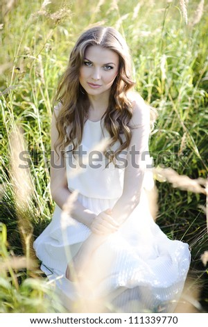 Beautiful blond girl seats in the high grass on the field.