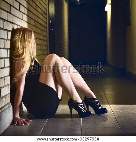 beautiful blond girl sitting on corridor floor - stock photo