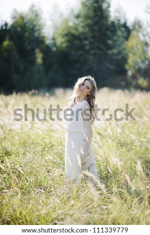 Beautiful blond girl stands in the high grass on the field.