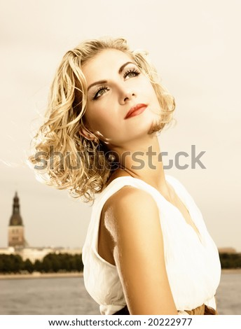 Beautiful blond girl stands near the river
