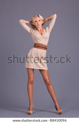 Beautiful blond girl with long legs standing  in a dress