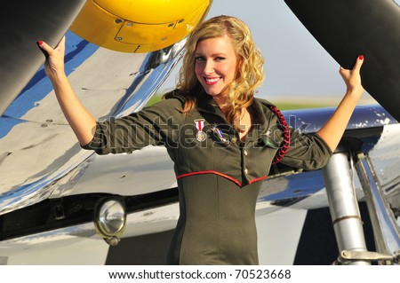 beautiful blond in an army uniform standing in front of a fighter plane