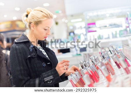 Beautiful blond lady testing  and buying cosmetics in a beauty store.