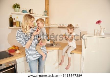 Beautiful blond lady trying to feed her upset baby. Adorable little girl sitting on kitchen counter and holding muffin stock photo