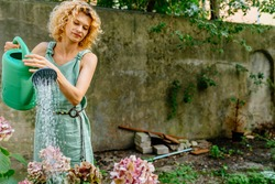 Beautiful blond mature woman gardening outside. Hydrangea need water. Female gardener with watering can outdoor in backyard. Hobbies and leisure, home gardening, houseplant, urban jungle concept.