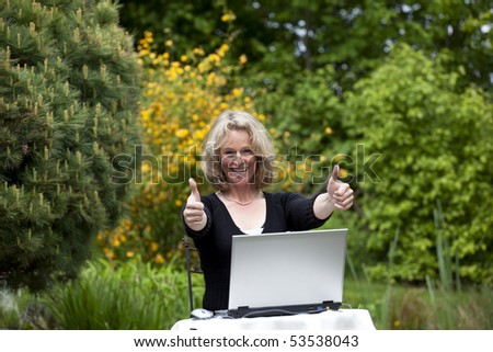 beautiful blond mature woman posing with both thumbs up