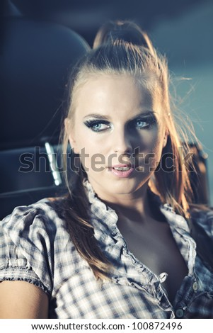 Beautiful blond model sitting on old car at night shot