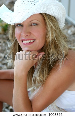 beautiful blond model wearing white top and white hat. Sunset in a country.