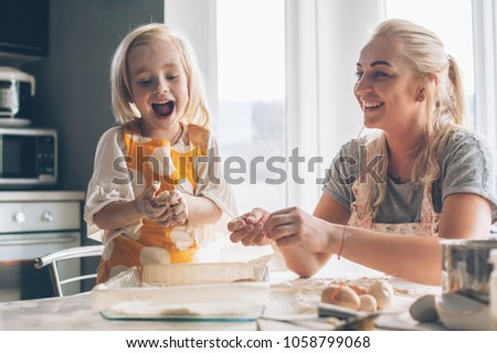 Photo of  Beautiful blond mom teaching her daughter cooking on the kitchen. Parent making everyday breakfast together with child. Family at home lifestyle photo.