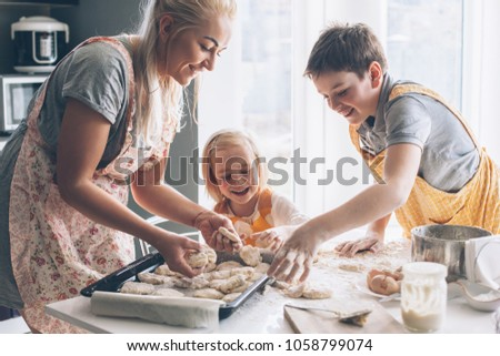 Beautiful blond mom teaching her two children cooking on the kitchen. Parent making everyday breakfast together with kids. Family at home lifestyle photo.
