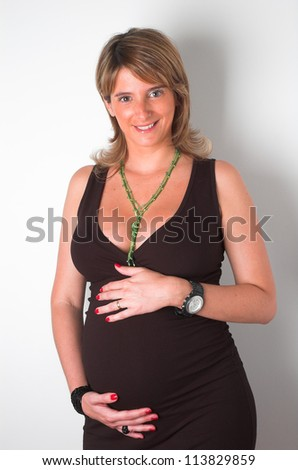 beautiful blond pregnant woman with her hands on the belly studio portrait