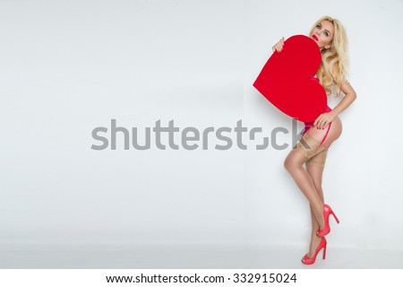 Stock Photo Beautiful blond sexy women model girl in love Valentine's Day with a red big heart to her face and red lips and red erotic lingerie long legs nude