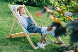 Beautiful blond slim graceful woman gardener relaxing in deckchair after working at garden outdoor. Slow living, gardening hobby concept.