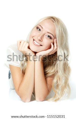 Beautiful blond teen girl lying, looking at camera and happy smiling. Isolated on white background - stock photo